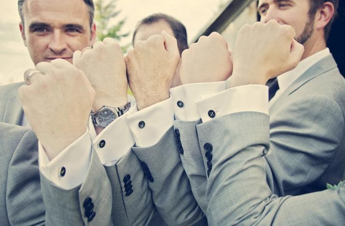 groom with groomsmen show off cufflinks