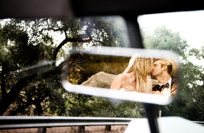 boho bride black tie groom kiss in vintage wedding car