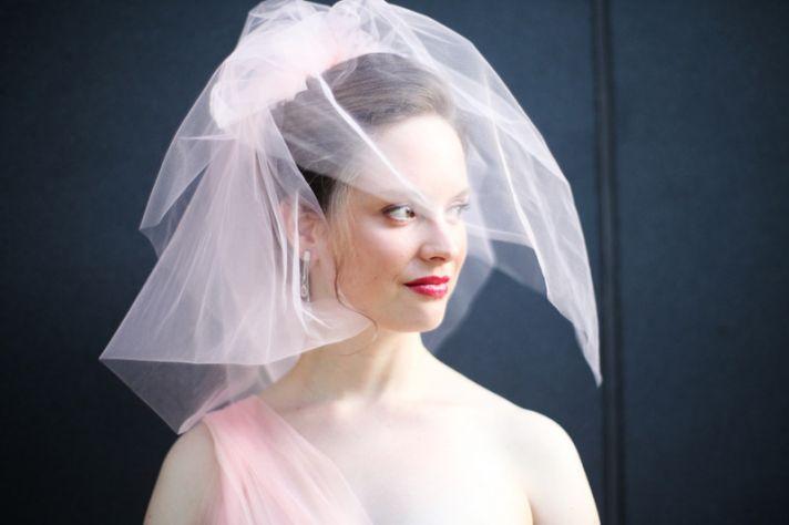 bride wears blush pink wedding dress birdcage veil