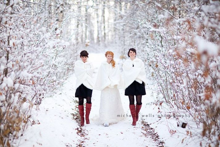 Winter bride walks through snow with bridesmaids