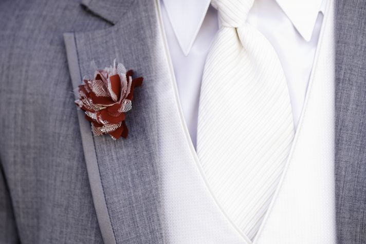Modern Groom Wears Gray Suit White Tie Red Boutonniere