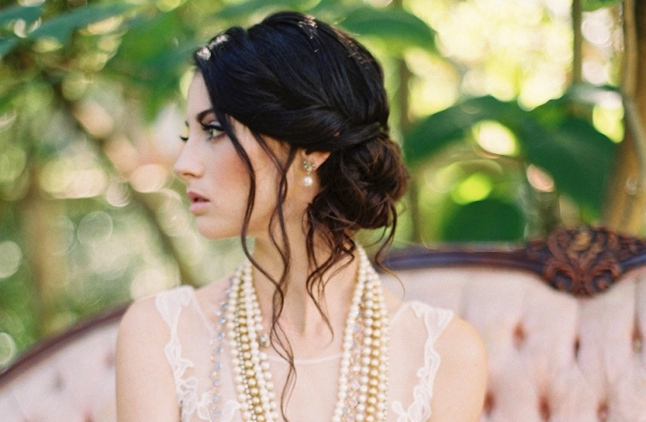 Low bun wedding hairstyle with tendrils framing the face