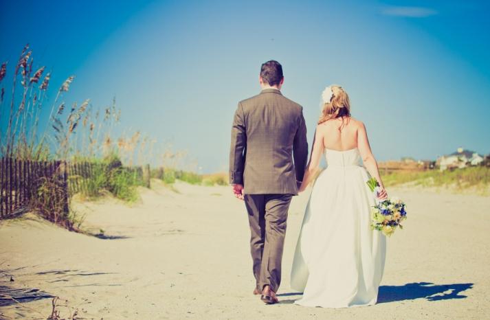 Beach bride and groom walk hand in hand
