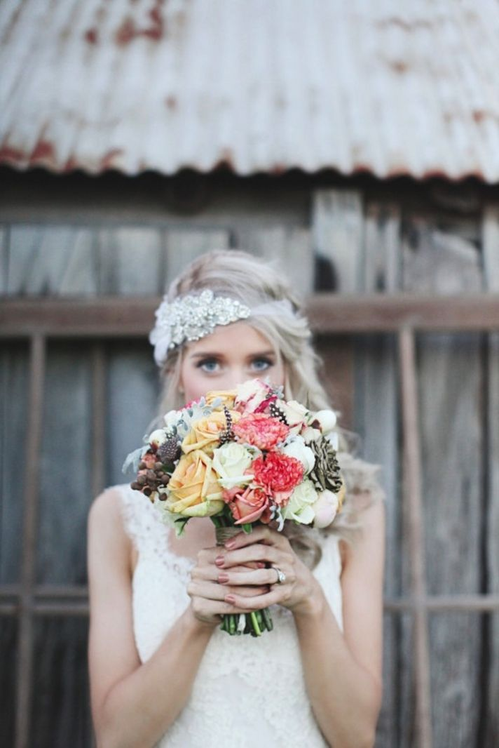 Bride wears beaded wedding bandeau holds romantic bouquet