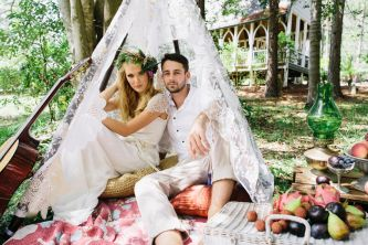 boho bride and groom pose beneath lace veil  teaser