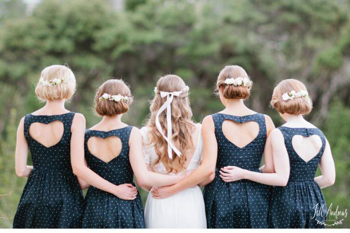 bridesmaids wear navy and white polka dot dresses with heart shaped open backs