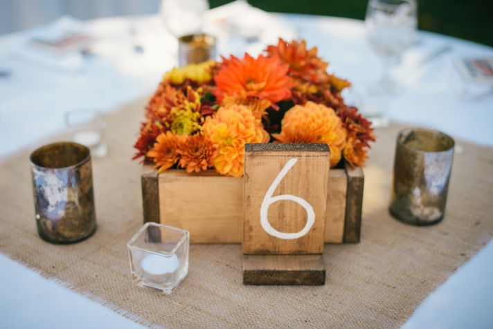 Rustic wedding reception tablescape with orange flowers burlap and wood