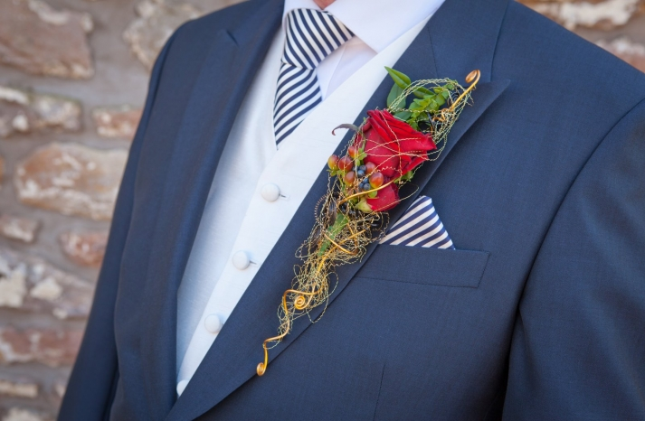 whimsical red rose grooms boutonniere