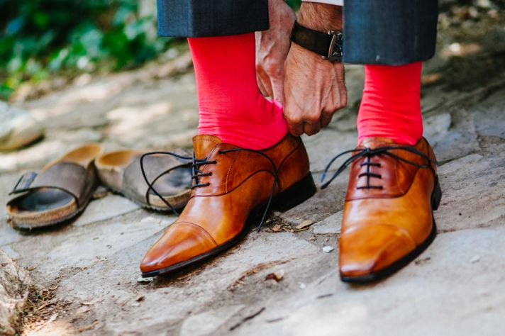 Grooms shoes with bright red socks