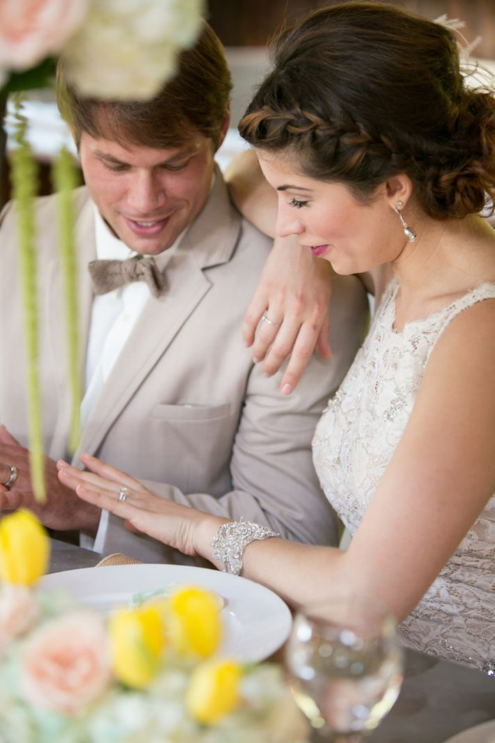 Bride and groom compare rings at reception