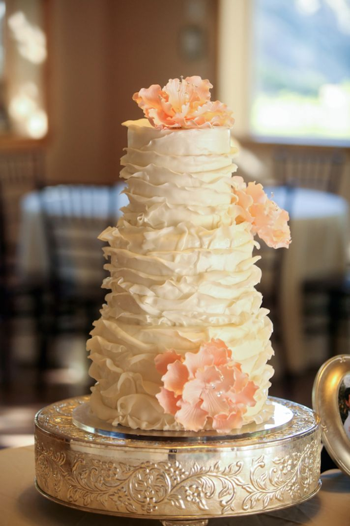 White ruffled wedding cake with peach sugar flowers